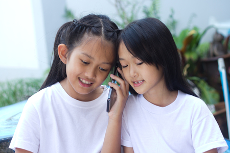 Two asian sister happy with cell phone