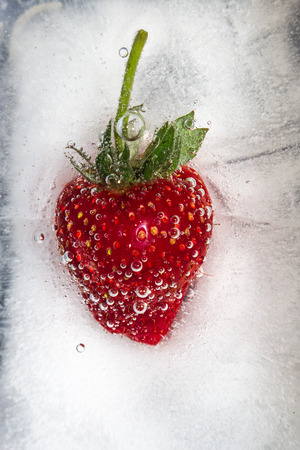 Ripe strawberry frozen in ice