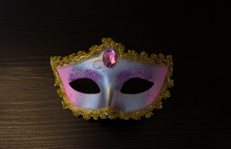 Carnival mask on black wooden background with night light