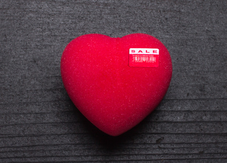 Heart for sale or Love for sale. Red heart shape with sale price tag on black board background Standard-Bild