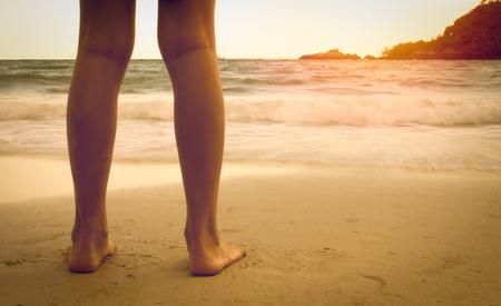 legs on the beach in the sunset Standard-Bild
