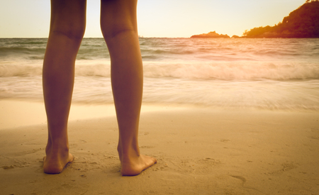 legs on the beach in the sunset Stock Photo