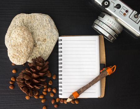 top view image of open blank notebook on black wooden table and old camera