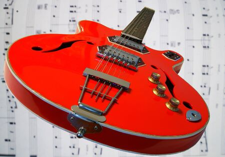 A red 12 string guitar on a music background Stock fotó