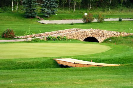 a stone bridge on a green golf course