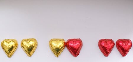 he is different: pairs of red and golden chocolate hearts Stock Photo
