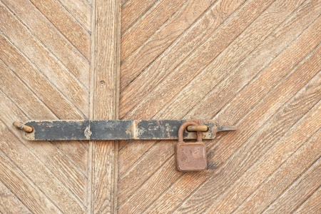 The old iron lock in a wooden door Stock Photo - 11446914