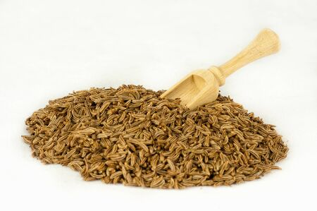 A pile of cumin seeds with a wooden spoon