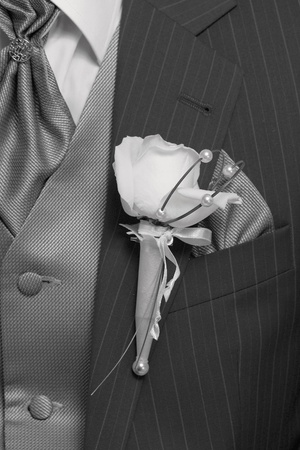 Groom in black wedding suits wearing rose boutonnieres