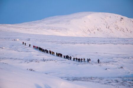 People are walking on the snow in Norway Stock Photo