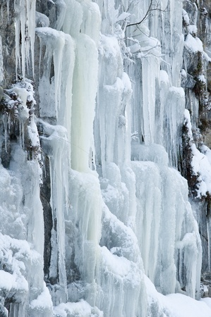 beautiful ice formation of frozen cascading water across a rock Stock Photo