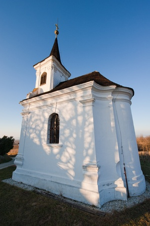 Small chapell on the hill at a wineyard with blue sky photo