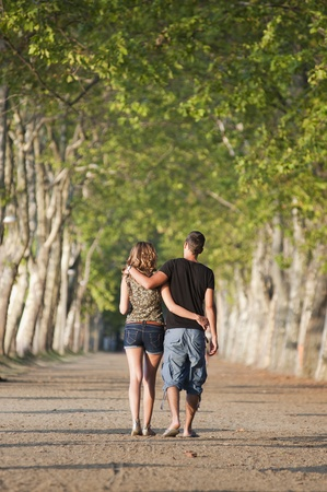 Young adult couple go for a walk in a park photo