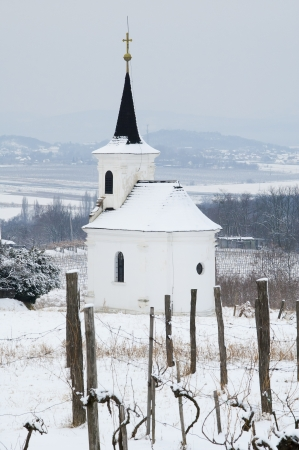 White small chapel on the hill in winter photo