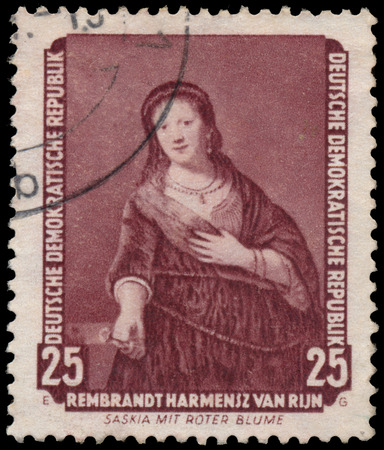 famous paintings: DDR - CIRCA 1957: A stamp printed in DDR shows the painting Saskia with red flower, by Rembrandt, from the series Famous Paintings from Dresden Gallery, circa 1957. Editorial