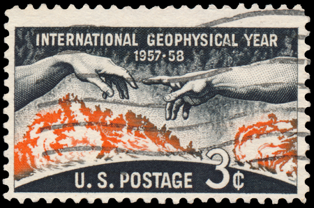 postmark: USA - CIRCA 1958: Stamp printed in United States of America shows Solar disc and hands from Michelangelo picture Creation of Adam, inscription and series Geophysical year 1957 - 1958, circa 1958