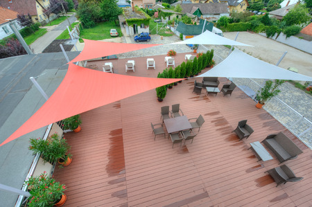 Terrace in summer with shade sails, flowers and deck chairs Фото со стока