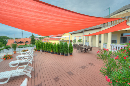 Terrace in summer with shade sails, flowers and deck chairs Archivio Fotografico