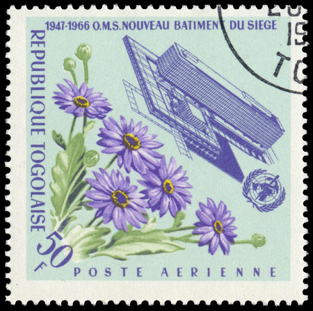 BUDAPEST, HUNGARY - 21 february 2016: a stamp printed in the Togo shows Headquarters of W.H.O. with flowers, circa 1966 Sajtókép