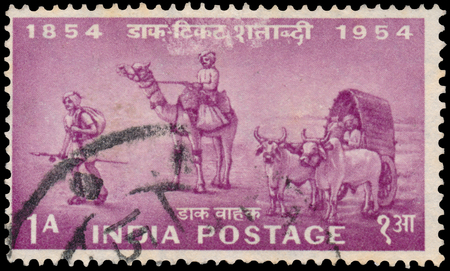 BUDAPEST, HUNGARY - 02 november 2015: Pink color postage stamp printed in India with image of Indian postal workers on foot, camel and the bullock cart to commemorate the centenary of Indian postage services; circa 1954
