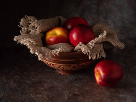 Ripe and juicy nectarines in a bowl on a table on a dark background. Rustic style.