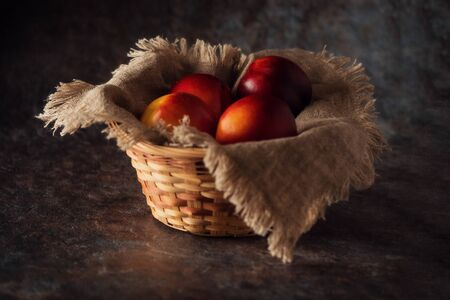 Ripe and juicy nectarines in a basket on a table on a dark background. Rustic style.