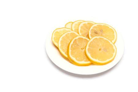Lemon sliced on a plate on a white background