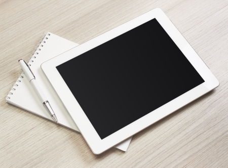 digital tablet on wooden tablets with notepad and pen