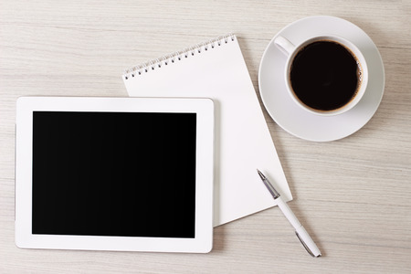 Digital tablet and cup of coffee on wooden table Stock Photo - 26585489