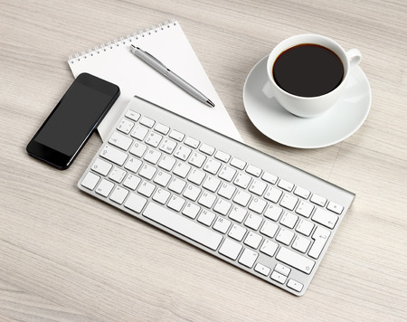 Computer desk with a cup of coffee, a notebook and pen photo