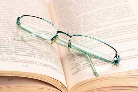 glases: Isolated stack of books with glases Stock Photo