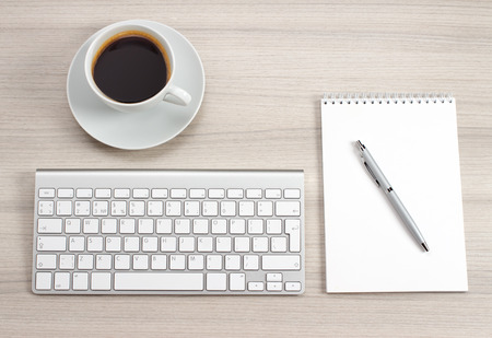 Workplace with notepad, coffee and keyboard