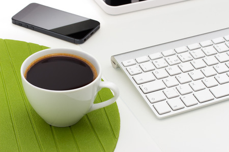 Coffee mug on the table with a phone and keyboard photo