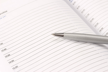 Diary with mortgaged pen on white background, isolated photo