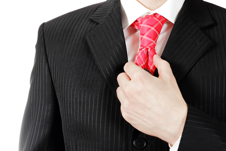 Businessman corrects tie red closeup photo