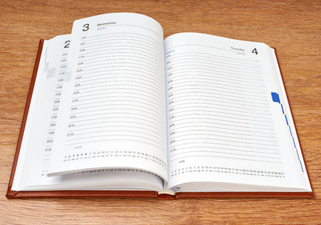 Daily planner with glasses and pen on the table photo