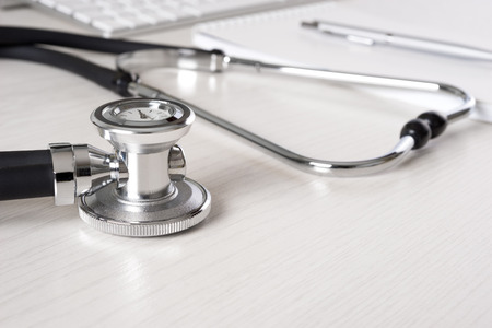 Stethoscope on doctors desk with keyboard and pad photo