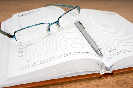 writ: Daily planner with glasses and pen on the table