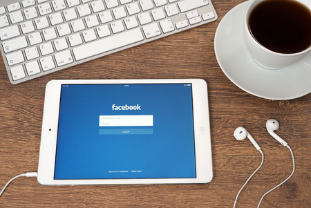 Ufa, Russia - May 04, 2015: iPad mini 2 with Facebook is an online social networking service on the screen. iPad mini 2 was created and developed by the Apple inc.