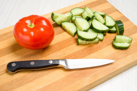 Board for cutting vegetables, a knife and cucumbers with tomatoes photo