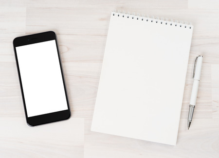 paper notes: Smartphone with white screen isolated with a notebook on a light background