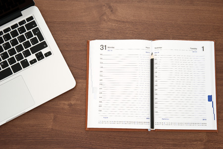 open diary: Diary and laptop on wooden table, top view Stock Photo