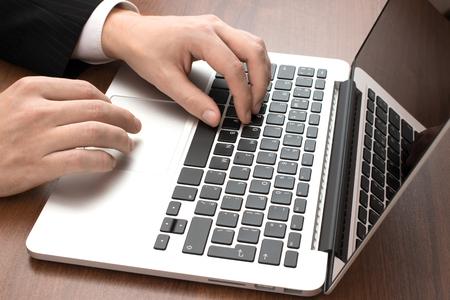typing: De negocios que trabaja en la computadora portátil primer plano
