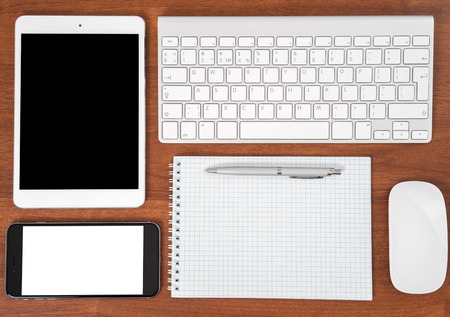 keyboard: Office table with notebook, computer keyboard and mouse, tablet pc and smartphone Stock Photo