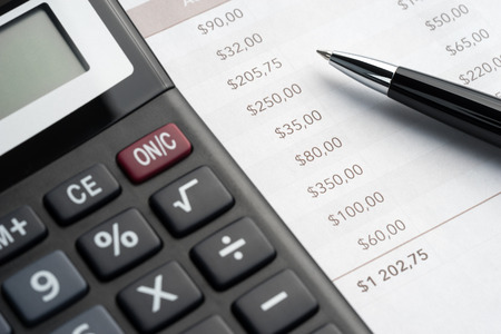year financial statements: Ballpoint pen, printed document and a large calculator on the table