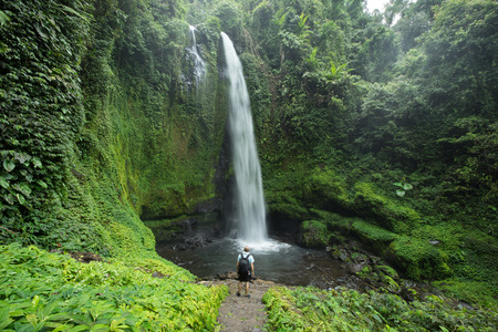 Man standing by huge tropical waterfall surrounded by lush green Rain forest vegetation and Jungle in Lombok, Indonesia