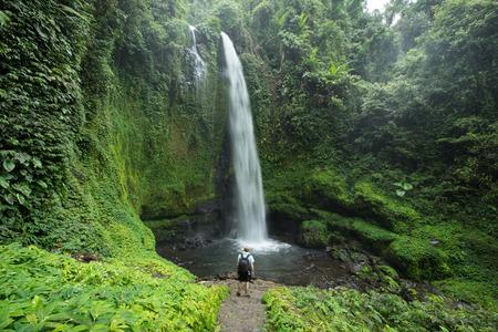Man staande door enorme tropische waterval omgeven door weelderige groene regenwoud vegetatie en Jungle in Lombok, Indonesië