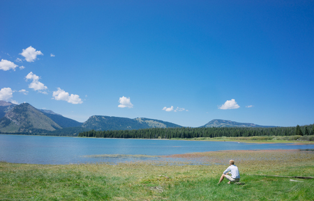 the next life: Man sitting next to idyllic lake taking in the tranquility and contemplating life and the beautiful view, Grand Teton National Park, USA