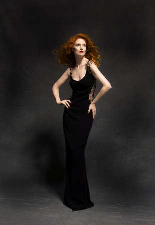 clothing: Classic redhead model in black dress in studio Stock Photo