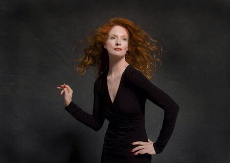 clothing: Classic redhead model in studio wearing black dress